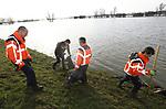 Foto: VidiPhoto<br /> <br /> SLIJK-EWIJK &ndash; Ze hebben ongetwijfeld al veel koeien, paarden en ander vee het leven gered, de mensen van dagbesteding Gidding Buiten-Zorg. Een groep van vijf mannen en &eacute;&eacute;n vrouw ruim dinsdag het zwerfafval op langs de Waaldijk bij het Gelderse Slijk-Ewijk. Zomers doen ze dat op de plekken waar veel gerecre&euml;erd wordt. Nu na de derde watergolf de rivier zich terugtrekt uit de uiterwaarden, blijft er veel levensgevaarlijk afval voor het vee, zoals blik, plastic en glas, achter. De mensen van Gidding hebben een verstandelijke en/of psychiatrische beperking, maar ze goed dat ze belangrijk werk verrichten. Opdrachtgever is Staatsbosbeheer.