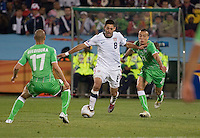 The USA's  Clint Dempsey (center) dribbles through the defense of Algeria's Adlane Guedioura (17), and Foued Kadir (21).  USA played Algeria in a 2010 FIFA World Cup first round match at Loftus Versfeld Stadium in Tshwane/Pretoria, South Africa on Wednesday, June 23, 2010. The USA defeated Algeria 1-0 to win Group C and advance to the second round of the 2010 FIFA World Cup.