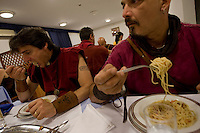 Roman legionnaires and gladiators, coming from the Gladiator School in Rome, eating pasta..
