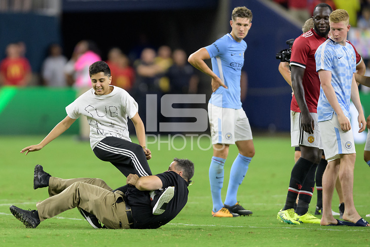 Houston, TX - Thursday July 20, 2017: Fan is tackled by stadium security after running onto the pitch during a match between Manchester United and Manchester City in the 2017 International Champions Cup at NRG Stadium.