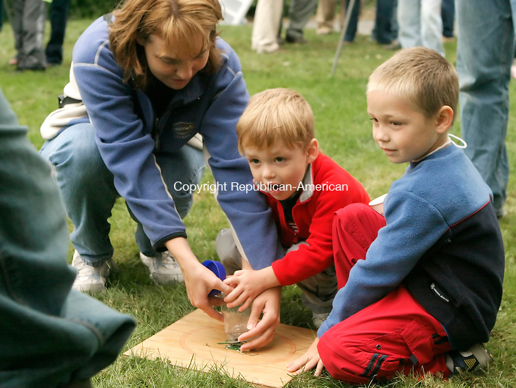 COLEBROOK, CT-02 AUGUST 2006-090206JS03-Amy Gardner of Colebrook, left, helps her sons Ethan, 3, and Seth, 5, get their frog in place during the frog jumping contest Saturday at the Colebrook Labor Day Fair held at the Colebrook Senior and Community Center.  -Jim Shannon Republican-American