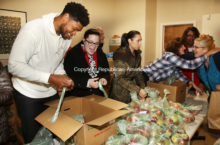 WATERBURY CT. 24 November 2015-112415SV01-From left, Ryan Gomes of Waterbury and Ashlee Honiker, 19, of  Newtown, Waterbury UConn student government, help hand out 372 meals to the needy at Greater Waterbury Interfaith Ministries in Waterbury Tuesday.<br /> Steven Valenti Republican-American
