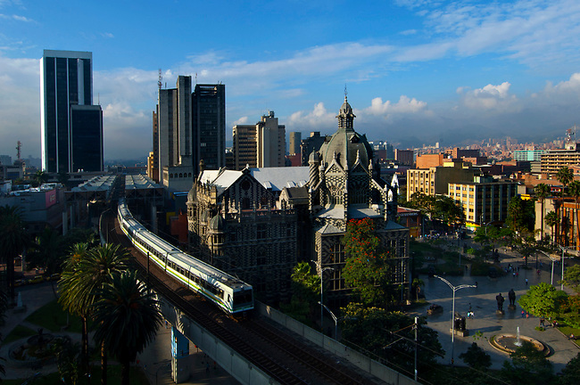 The elevated Medellin Metro is in motion as it glides out of Parque Berrio Station in front of Plaza Botero.  The striped art nouveau Palace of Culture and downtown office buildings can be seen in the background.