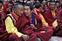 Buddhist monks talk at the Cham Dances, Katok Dorjeden Monastery - Kham, (eastern, Tibet), Sichuan Province, China