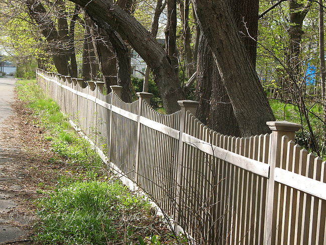 Picket fence bordering property with trees.
