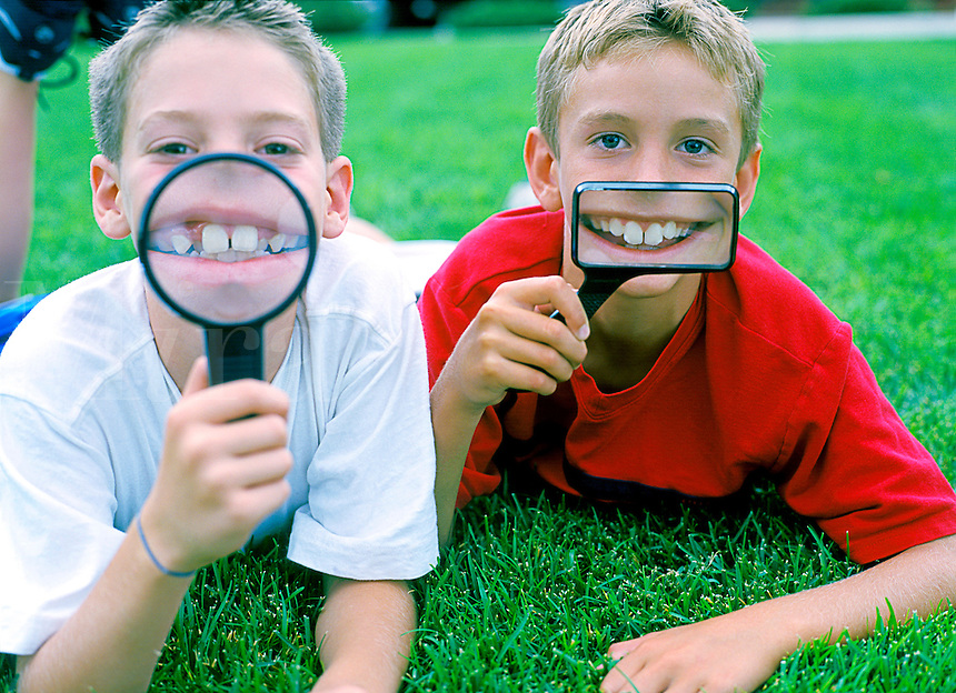 Youthful boys with magnifying glasses in front of their faces.
