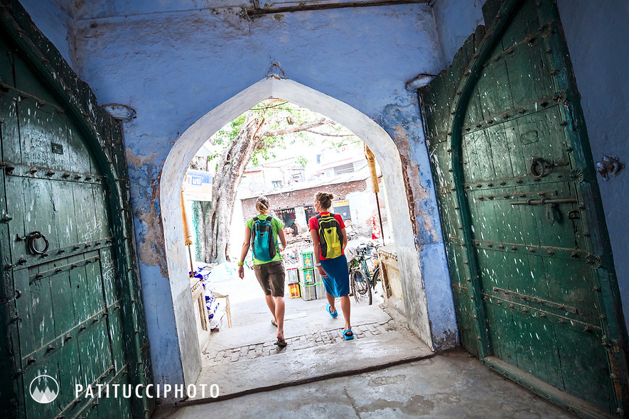 Two female travelers walk throiugh a colorful door in the town of Rishikesh, India