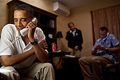 United States President Barack Obama makes phone calls to 10 American service members stationed around the world, from his vacation rental home in Kailua, Hawaii, December 24, 2011. White House Communications Agency (WHCA) Presidential Communications Officer CPT Mallory Fritz and Military Aide Lieutenant Colonel Sam Price coordinate the calls in the background. .Mandatory Credit: Pete Souza - White House via CNP