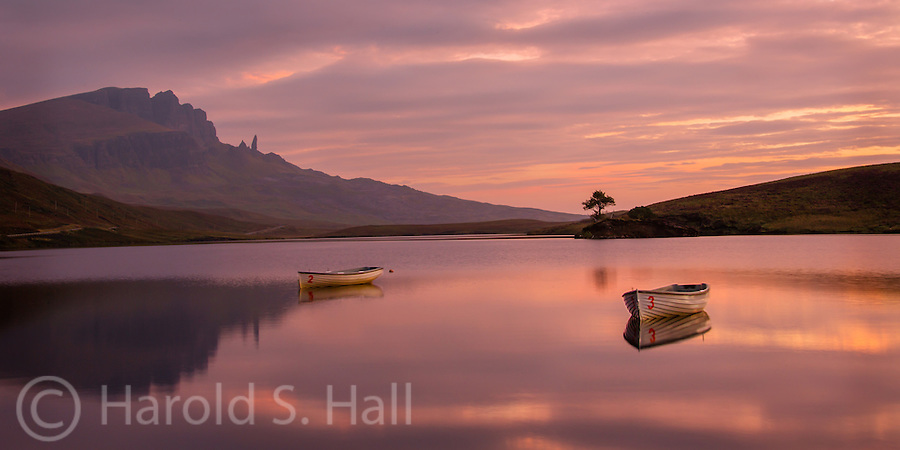 The Old Man of Storr is the monolith appearing rock in the distance and reflecting in Loch Fada.  Despite this lake being quite calm and there being no real detectable breeze, surprisingly, the two boats were spinning around rapidly .  Longer camera shutter exposures resulted in very blurred boats due to this boat movement.  If there was a wind, there would have been ripples in the lake surface. The lone tree is really on an island in the middle of the loch.