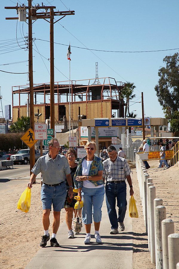 Tourists returning to California from Los Algodones, B.C, Mexico with shopping bags.