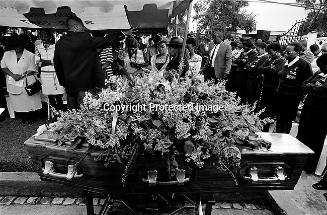 An unidentified Nigerian minister preaches during a funeral for Jessica Ngcongwane, age 28, who died a few days earlier in an Aids related disease on May 3, 2003 in Soweto, South Africa. Her family decided to come out in public about her disease to help other people get rid of the stigma about Aids in their community. South Africa has one of the highest aids infection rates in the world and its estimated that about one thousand people die each day. (Photo by: Per-Anders Pettersson)