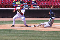 Cedar Rapids Kernels third baseman Jonathan Hinojosa (4) slides in to third base as Wisconsin Timber Rattlers third baseman Sthervin Matos (9) takes the throw during a game against the Cedar Rapids Kernels on April 23rd, 2015 at Fox Cities Stadium in Appleton, Wisconsin.  Cedar Rapids defeated Wisconsin 3-0.  (Brad Krause/Four Seam Images)
