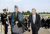 Washington, DC - June 14, 2004 -- United States Secretary of Defense Donald H. Rumsfeld (right) escorts President Hamid Karzai of Afghanistan (center) through an honor cordon and into the Pentagon in Washington, D.C. on June 14, 2004.  The two men will meet to discuss a range of security issues particular to Afghanistan and its immediate neighbors.  .Credit: Robert D. Ward / DoD via CNP
