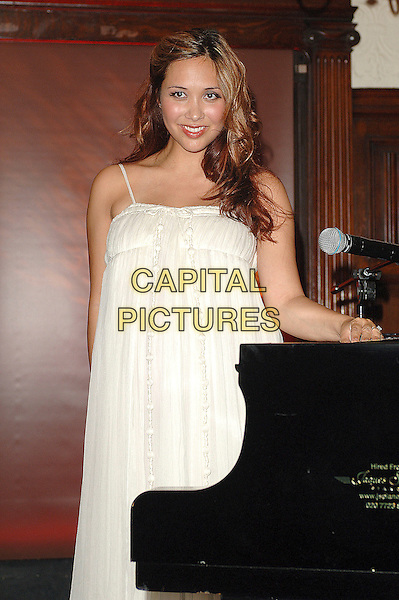 """MYLEENE KLASS.hosts a party to celebrate the release of her new classical album """"Music For Romance"""" at Kettners, London, England,.2nd July 2007.half length piano Pregnant white dress.CAP/ BEL.©Tom Belcher/Capital Pictures."""
