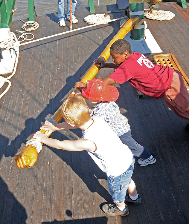 Children trying their hands at the tiller of the Sloop Clearwater at the Pumpkin Sail Festival at Hudson, NY on Monday, October 10, 2011. Photo by Jim Peppler. Copyright Jim Peppler/2011.