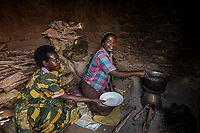 Uganda, Wamala. Mayi Nankya using her a BioLite wood cook stove at home. Serving beans to her friend, Mariam Ndagine.