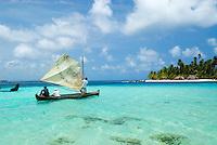 Traditional dugout sailboat plys the turqouise waters off Achutupu (Isla de los Perros)  in the Comarca De Kuna Yala, San Blas Islands, Panama
