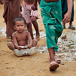 A Rohingya refugee child holds on tight as another child pulls them along the dirt street in the sprawling Kutupalong Refugee Camp near Cox's Bazar, Bangladesh. More than 600,000 Rohingya refugees have fled government-sanctioned violence in Myanmar for safety in this and other camps in Bangladesh.
