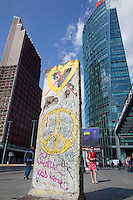 "A remaining fragment of the Berlin Wall in Potsdamer Platz. In the background is the Sony Centre, the Deutsche Bahn HQ, and the entrance to the Potsdamer Platz U-Bahn station which was a ""ghost station"" through which trains passed but could not stop during the years of the Wall and the Cold War."