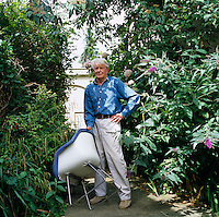 Designer Robin Day stands in his Chichester garden holding one of his designs