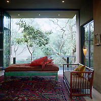 Floor-to-ceiling glass doors fold back to link the living area with the terrace and the surrounding tree tops