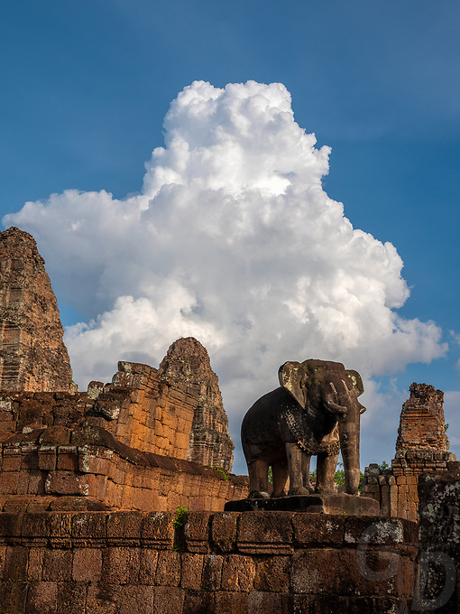 TheEast Mebona 10th Centurytempleat Angkor, Cambodia. Built during the reign of King Rajendravarman,Interesting are the carved standing Elephants on the corners. Cambodia Monsoon clouds over one of the Elephants