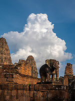 The East Mebon a 10th Century temple at Angkor, Cambodia. Built during the reign of King Rajendravarman, Interesting are the carved standing Elephants on the corners. Cambodia Monsoon clouds over one of the Elephants