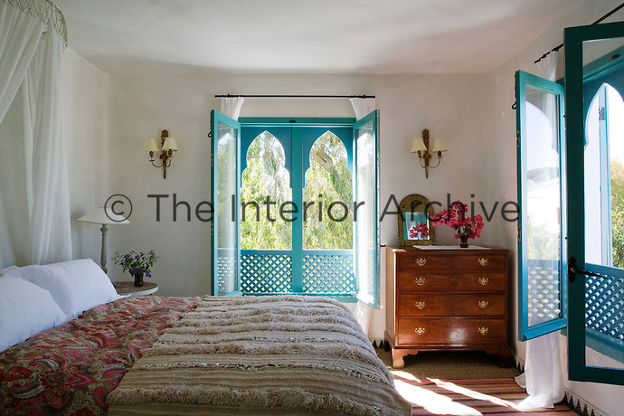 One of the simple, airy bedrooms surrounded by cheerful turquoise windows. The bed is covered with a Moroccan wool rug