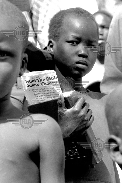 © Crispin Hughes / Panos Pictures..Narus, Eastern Equatoria, Southern SUDAN..A boy clutching his bible at an outdoor Catholic church service conducted by Father Placido Alema.