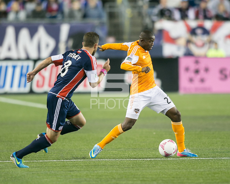 Houston Dynamo midfielder Oscar Boniek Garcia (27) controls the ball as New England Revolution defender Chris Tierney (8) prepares to tackle.  The New England Revolution played to a 1-1 draw against the Houston Dynamo during a Major League Soccer (MLS) match at Gillette Stadium in Foxborough, MA on September 28, 2013.