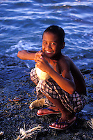 Filipino boy opening a coconut by hand next to the sea