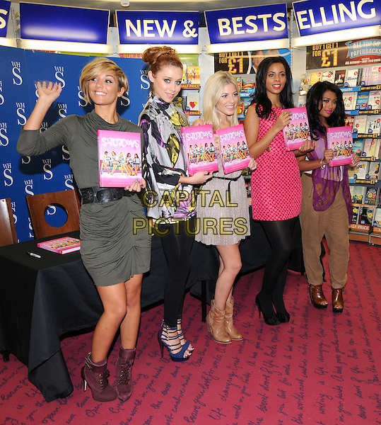 "THE SATURDAYS - Frankie Sandford, Una Healy, Mollie King, Rochelle Wiseman & Vanessa White .The Saturdays sign copies of their new book ""Our Story!""  at WH Smith, Bluewater Shopping Centre, Greenhithe, Kent, England, UK, 16th October 2010..full length girl band group holding books purple ankle boots brown lace-up green dress belt booksigning signing black tights leggings pink grey gray purple skull print scarf top khaki trousers sandals blue platform open toe hand waving .CAP/BRC.©Ben Rector/Capital Pictures."