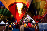 ballons at the Albuquerque balloon festival about to lift of with large gass flames