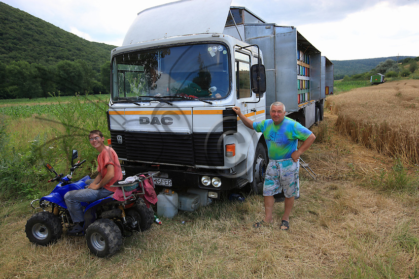 On the road to the village of Ciucurova, Francise Gadri, 52 years old, and his 17-year-old son Gheorghe proudly pose in front of their 152 hives in a brand new fitted truck.