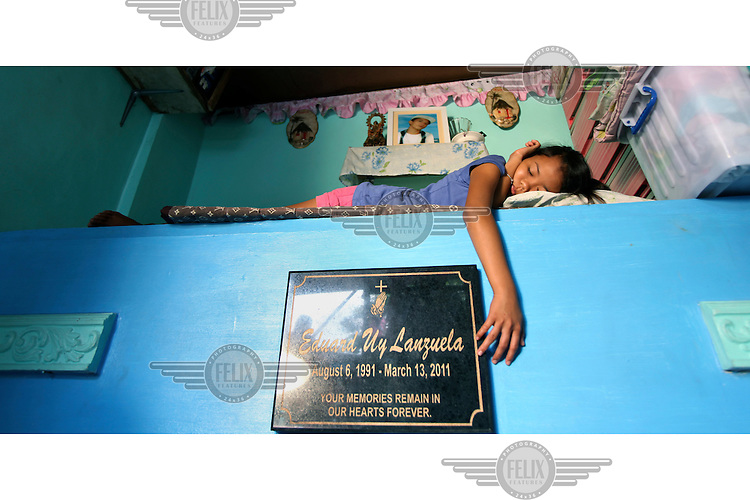 14 year old Jessica, who lives with her family in one of Manilla's largest cemeteries, sleeps on her brother's tomb that is incorporated into the family home. He was killed by  a car as he made his way home after finishing work. Her parents are caretakers at the cemetery, and although they live without access to clean water or electricity, and under the threat of eviction, they prefer to live there because it is clean and far from the crime-ridden slums.