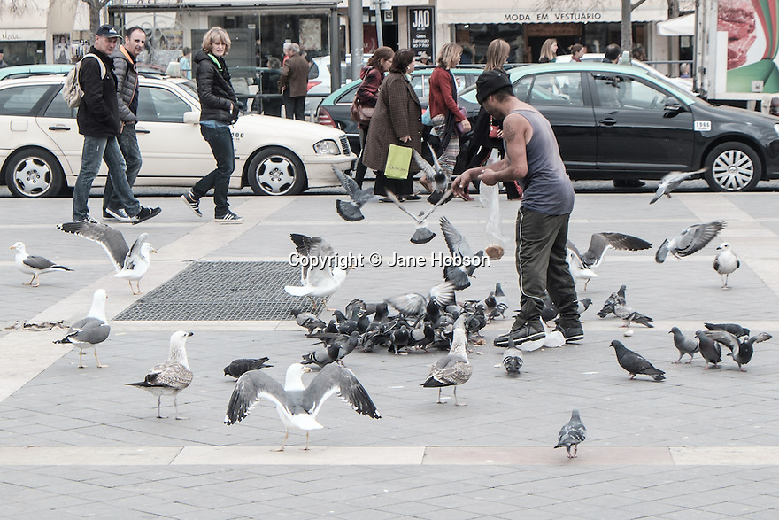Lisbon, Portugal. 21.03.2015. a homeless man feeds the birds in Praça da Figueira. © Jane Hobson.