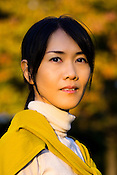 A young Japanese woman enjoying autumnal views in a park.