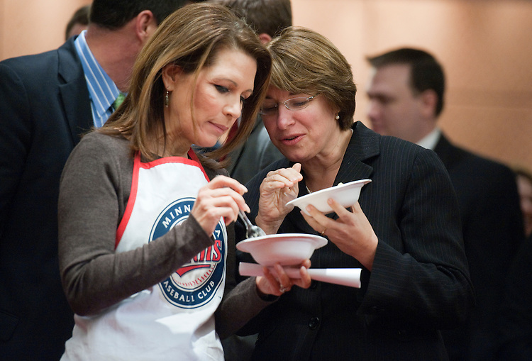"UNITED STATES - MARCH 07:  Rep. Michele Bachmann, R-Minn., left, and Sen. Amy Klobuchar, D-Minn., confer during the second annual ""hotdish"" competition in the Capitol Visitor Center, featuring casserole-like dishes from members of the Minnesota Congressional Delegation.  The dishes of Sen. Al Franken, D-Minn., and Rep. Chip Cravaack, R-Minn., tied for first place in the competition.  (Photo By Tom Williams/CQ Roll Call)"