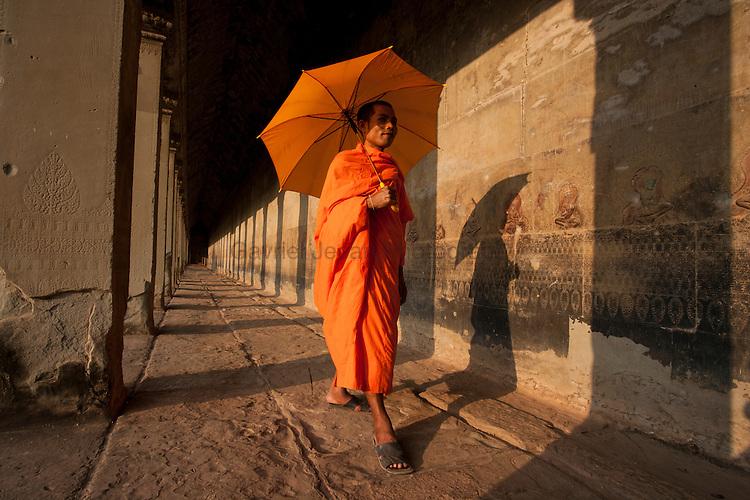Monk walking among the columns of the gallery at Angkor Wat.