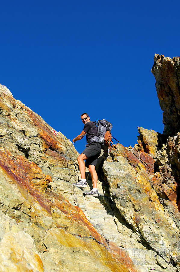 Man climbing a rock ridge on safety chain