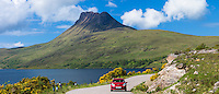 Motorist on touring holiday by Stac Pollaidh, Stack Polly mountain in Inverpolly National Nature Reserve in Coigach area of North West Highlands Geopark, Scotland
