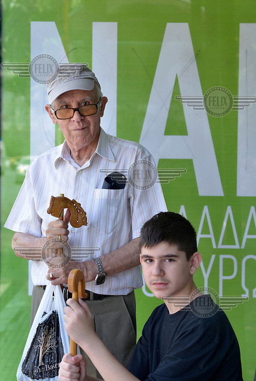Spiros Chryssanthakis, an 81 year old retired doctor, and his grandson waiting at a bus stop beside a huge 'Nai' ('Yes') poster. Spiros plans to vote Yes in the referendum saying: 'Our future is in Europe, especially for our youth.'   On 5 July 2015 Greeks voted in a referendum to acceptance or reject economic reforms demanded by the country's creditors. The outcome could determine whether or not Greece remains in the Eurozone and if it will continue to receive further financial assistance from the 'Troika' of the IMF, EU and European Central Bank.