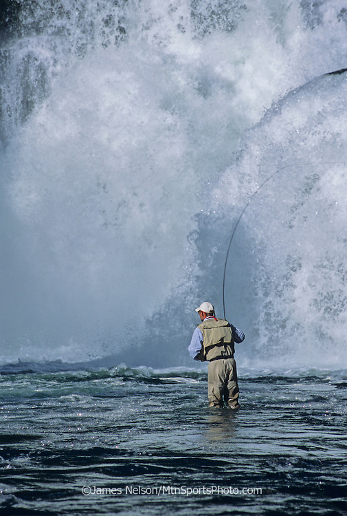 08762-C. An angler casts a fly for trout at the base of Lower Mesa Falls on the Henry's Fork of the Snake River in Idaho.