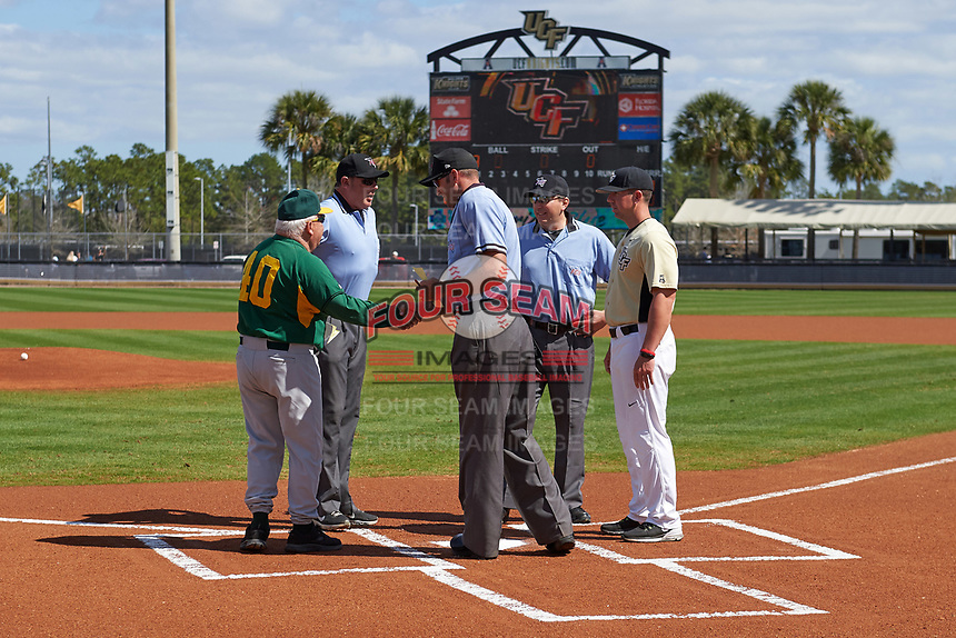 Siena Saints head coach Tony Rossi (40) during the lineup exchange with UCF Knights assistant coach Brandon Romans (9) and umpires Travis Carlson (center), Josh Miller (right), and Hank Himmanen (left) on February 21, 2016 at Jay Bergman Field in Orlando, Florida.  UCF defeated Siena 11-2.  (Mike Janes/Four Seam Images)