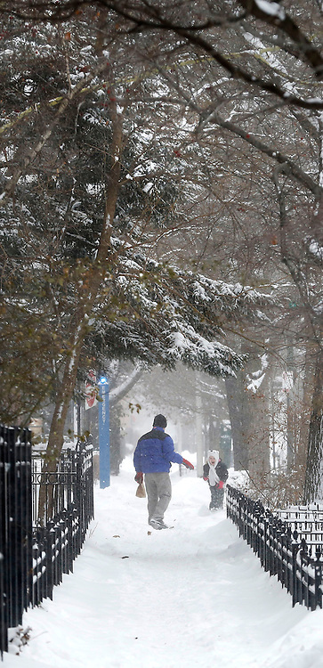 People enjoy the snow as it falls on the Lincoln Park campus of DePaul University in Chicago as the New Year brought two days of lake effect snow and ice. (Photo by Jamie Moncrief)