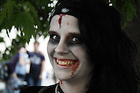 Young woman with black hair, painted white in the face, with theater blood in her forehead and around the mouth. Waiting for the Zombie walk in prague to start.