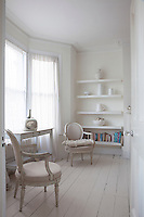 White shelves display white ceramics in one of the alcoves of the guest bedroom