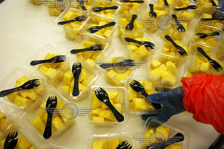 A Blue Skies employee organises packages of cut pineapple at the Blue Skies factory outside of Nsawam. Much of the fresh fruit produced at Blue Skies is exported.