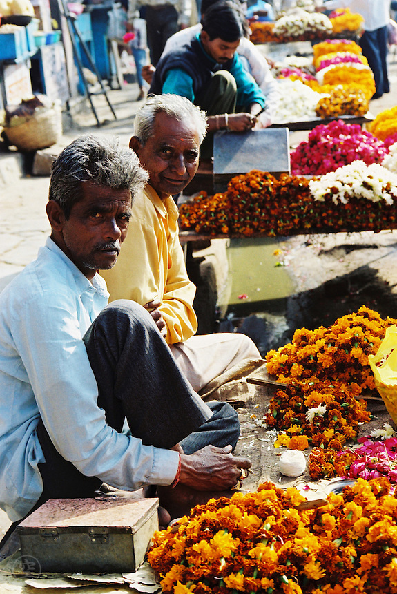 Men selling marigolds at a flower market in India look directly at the camera.