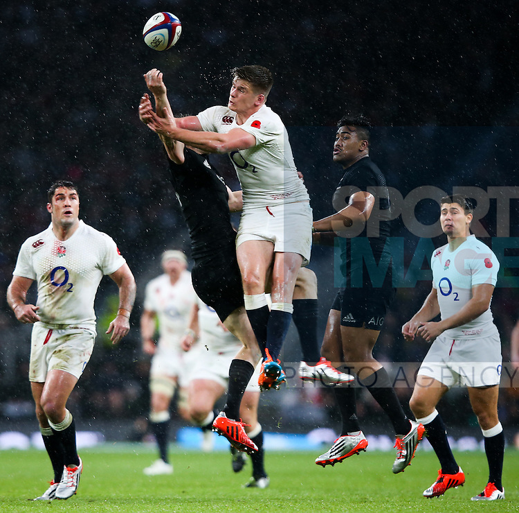 England's Owen Farrell takes a fist in the face from New Zealand's Aaron Cruden - QBE Autumn Internationals - England vs New Zealand - Twickenham Stadium - London - 08/11/2014 - Pic Charlie Forgham-Bailey/Sportimage